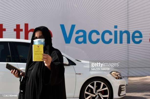 Woman displays her COVID-19 vaccine certificate in front of the Bahrain International Exhibition and Convention Center in the capital Manama, on...