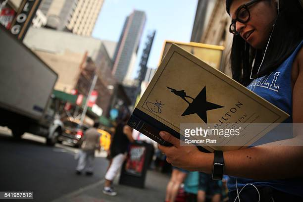 Woman displays her Hamilton autograph book outside of the the popular Broadway show Hamilton on June 21, 2016 in New York City. The Tony...
