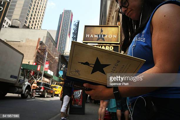 A woman displays her Hamilton autograph book outside of the the popular Broadway show Hamilton on June 21 2016 in New York City The Tony Awardwinning...