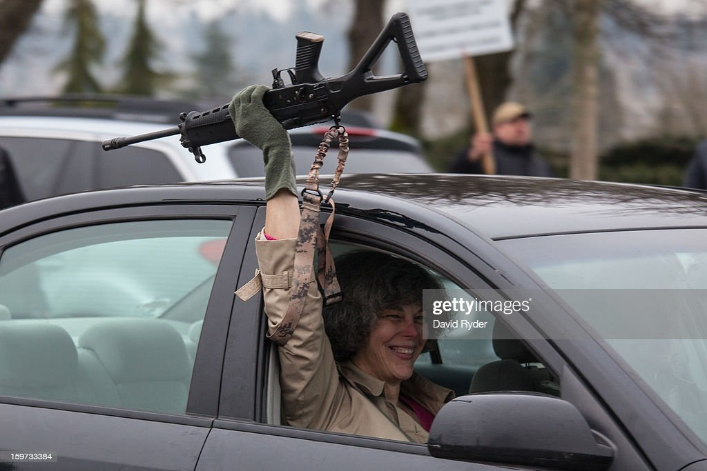 A woman displays her rifle to fellow demonstrators during a pro-gun rally on January 19, 2013 in Olympia, Washington. The Guns Across America national campaign drew thousands of protesters to state capitols, including over 1,000 in Olympia.