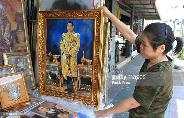 Woman displays pictures of Crown Prince Maha Vajiralongkorn for sale at a royal memorabilia shop in Bangkok on 29 November 2016 during Thailand's...