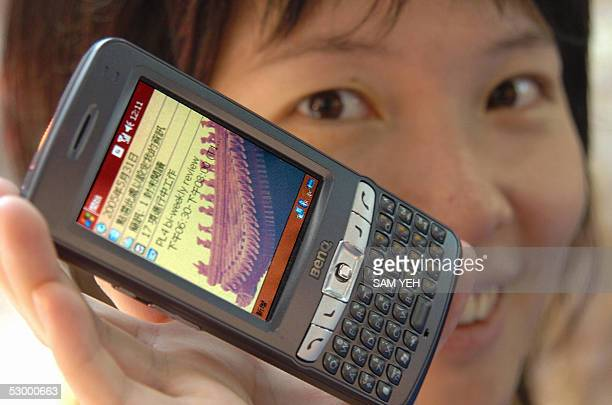 Woman displays the latest smart PDA phone during the Computex Taipei at World Trade Center 31 May 2005. Some 2,828 booths from 1,347 companies are...