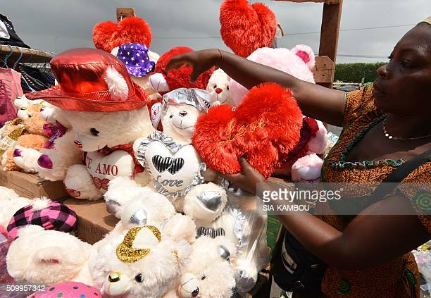Woman displays Valentine's day item on February 13, 2016 in a street market in Marcory, a popular suburb of the Ivorian capital. / AFP / SIA-KAMBOU