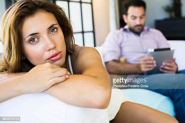 Woman displeased by boyfriend on digital tablet