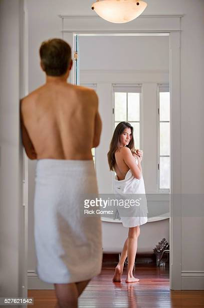 Woman disrobing in bathroom while man watches her