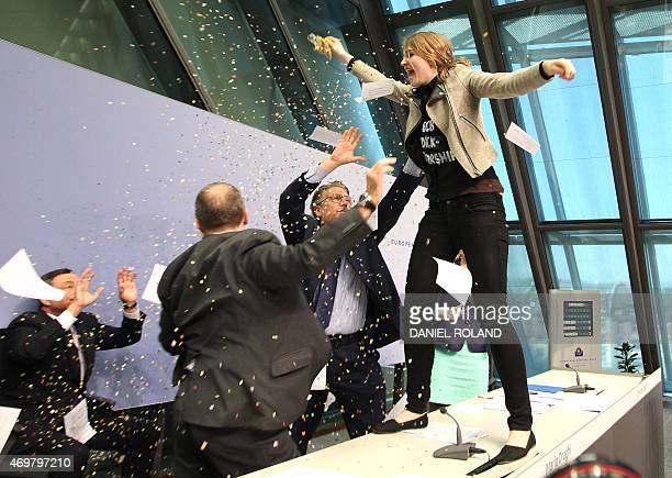 A woman disrupts a press conference by Mario Draghi President of the European Central Bank by throwing confettis following a meeting of the Governing...