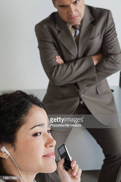 Woman distractedly listening to MP3 player at work, angry boss in background