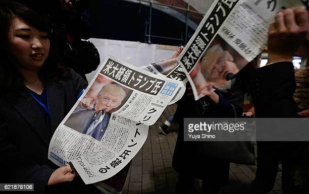A woman distributes an extra edition of a newspaper featuring a front page report on the US Presidential Election and Republican Presidentelect...