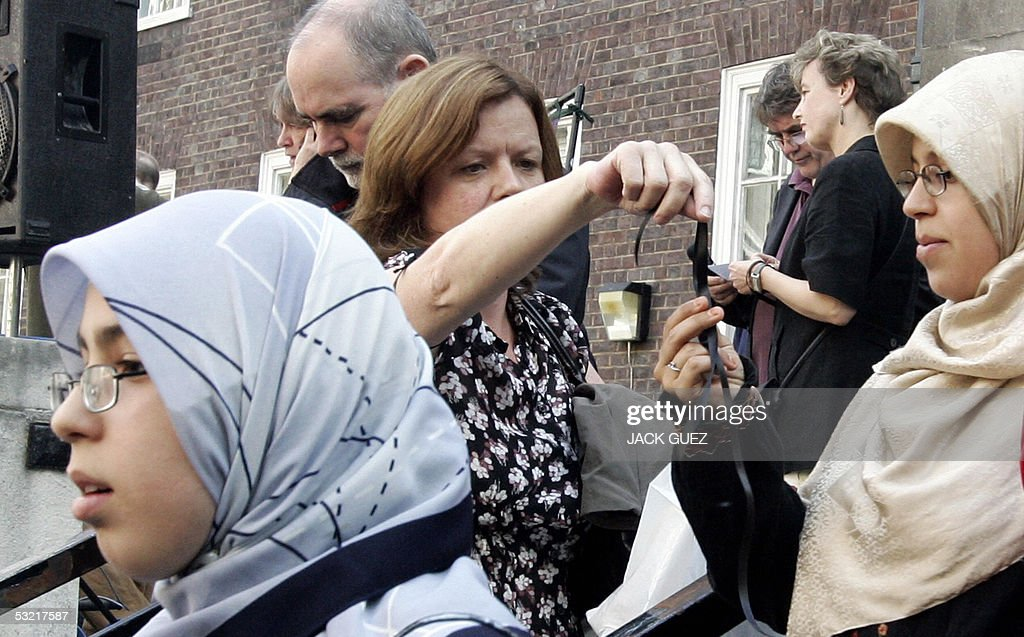 A woman distributes black ribbons during a gathering 09 July 2005 to remember the victims of the London bombings that killed at least 50 people and injured some 700.