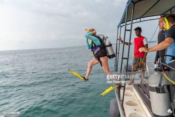 een vrouw - duiker die een duikpak en aqualung draagt, springt aan de oceaan van een boot. - aqualung diving equipment stockfoto's en -beelden
