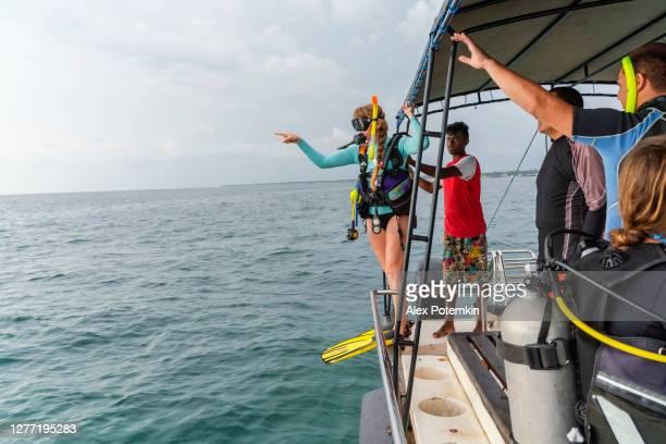 een vrouw - duiker die een duikpak en aqualung draagt, bereidt zich voor om aan de oceaan van een boot te springen. - aqualung diving equipment stockfoto's en -beelden