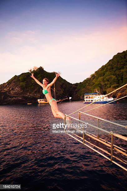 A woman dives from a boat into blue waters.