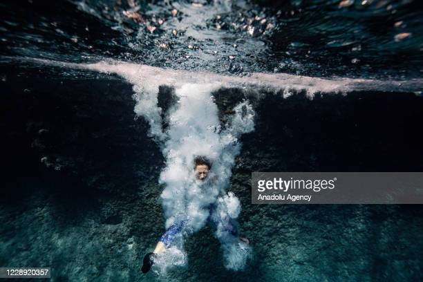 """Woman dives into the clear water of """"Suluada"""" located 7 kilometers from another favorite spot location for deep water soloing Cape Gelidonya, in..."""