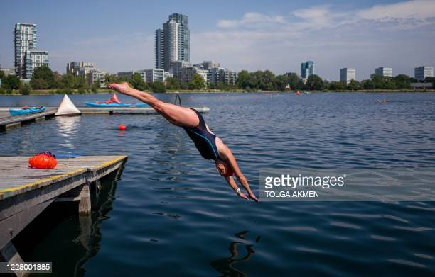 Woman dives into the water as people enjoy open water swimming at the West Reservoir Centre in north London on August 11, 2020 during a Summer...