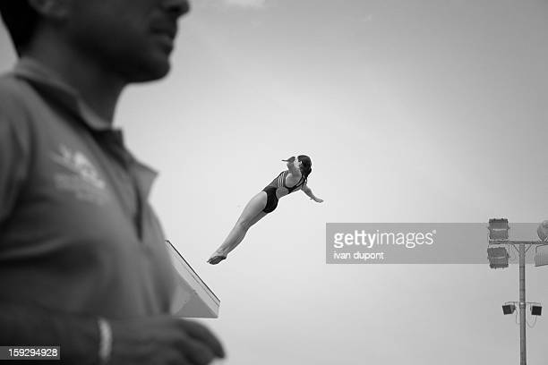 Woman diving from a platform, woman in the air, image in black and white, back dive strait, sport championships, acrobatic diving