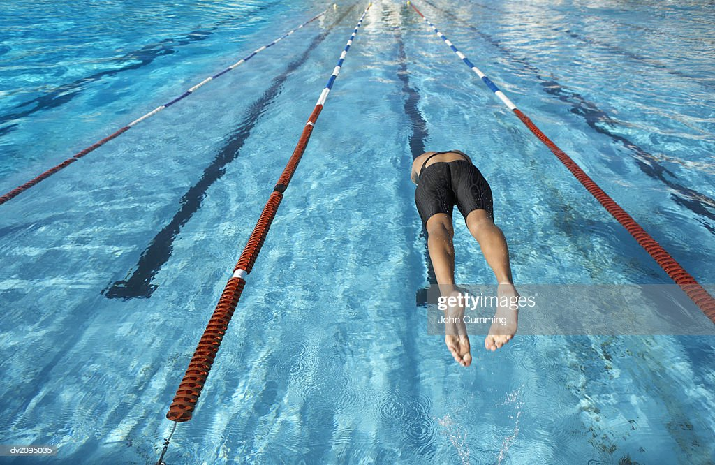 Woman Diving Into a Swimming Pool : Stock Photo