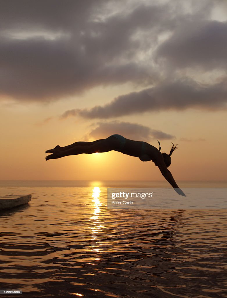 woman diving into sea at sunset : Stockfoto