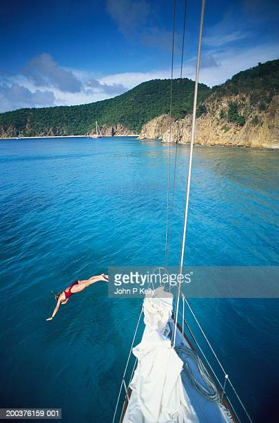 Woman diving into sea from bow of sailboat, elevated view