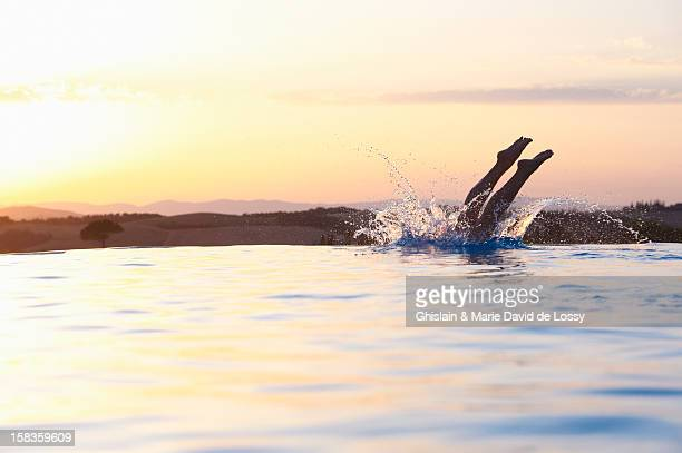 woman diving into the swimming pool - diving into water stock pictures, royalty-free photos & images