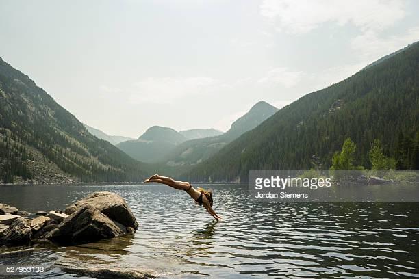 A woman diving off a rock.