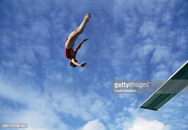 Woman diving off diving board, low angle view (Digital Composite)