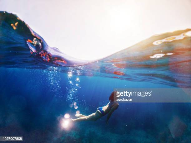 woman diving under the sea - light natural phenomenon stock pictures, royalty-free photos & images