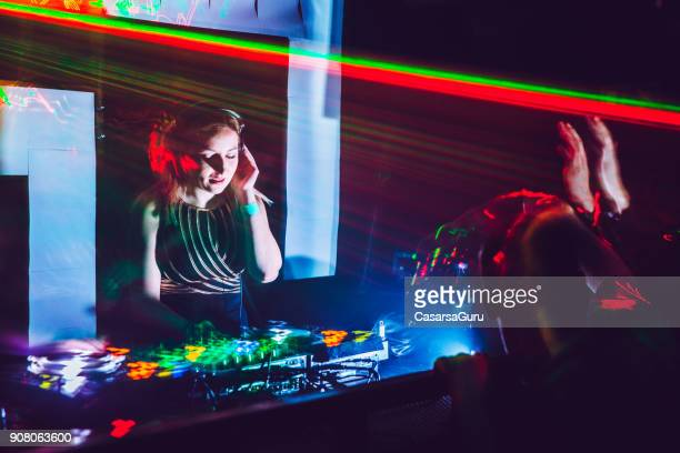 Woman DJ Mixing Music on Stage