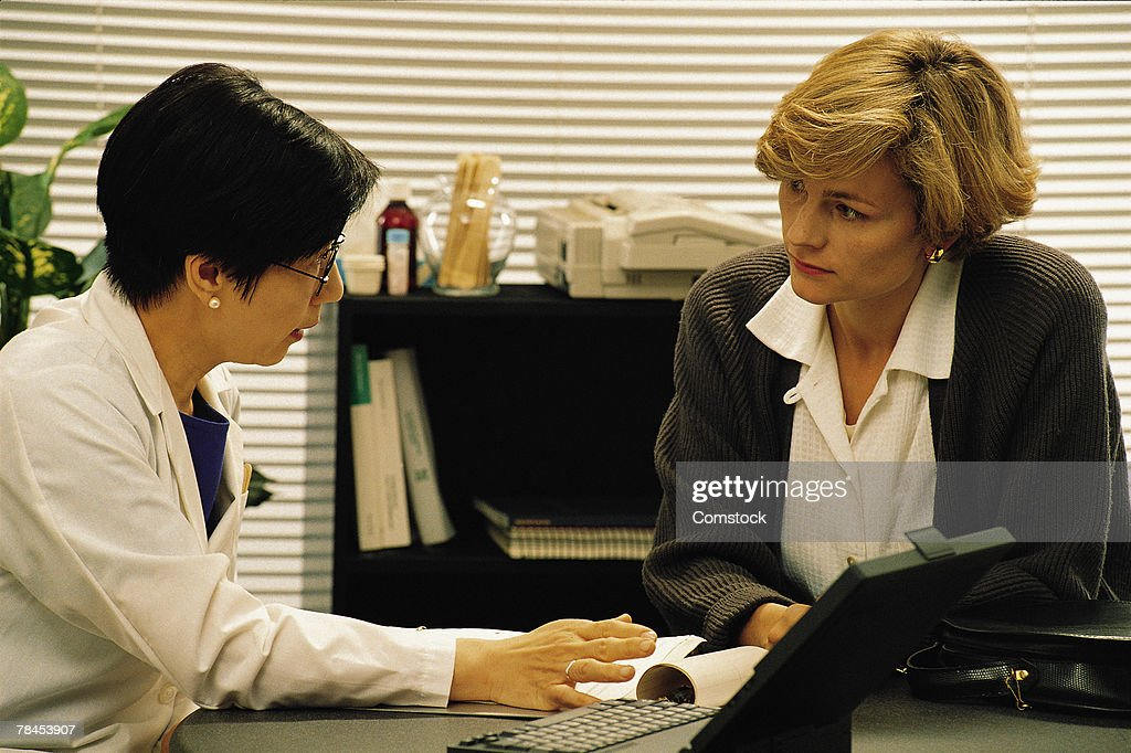Woman doctor in her office consulting with patient : Stockfoto