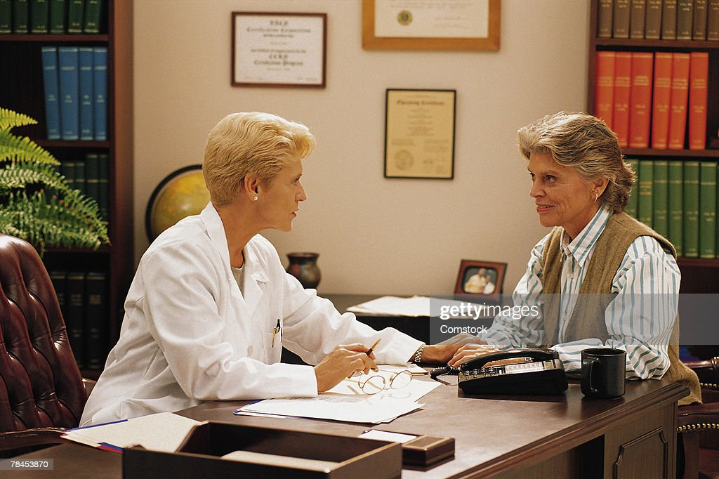 Woman doctor in her office with woman patient : Stockfoto