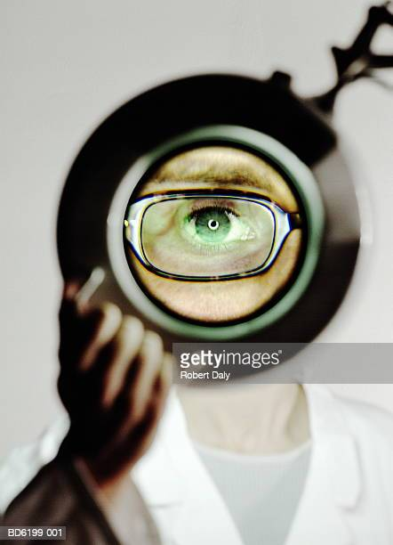 Woman doctor looking through magnifying lens