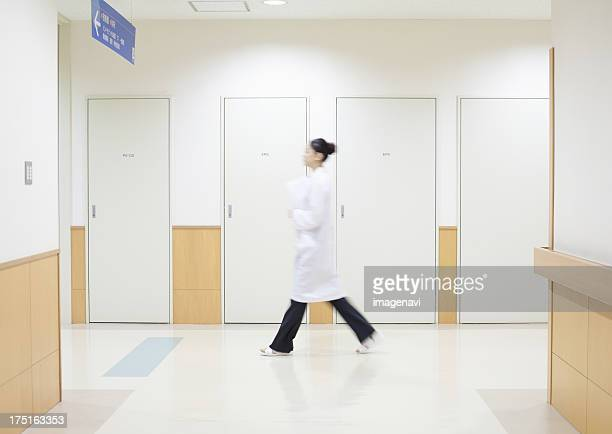 Woman doctor walking along corridor