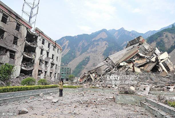 A woman documents the remains of a demolished school in the devastated town of Yingxiu on May 22 2008 in southwest China's quakestricken Sichuan...
