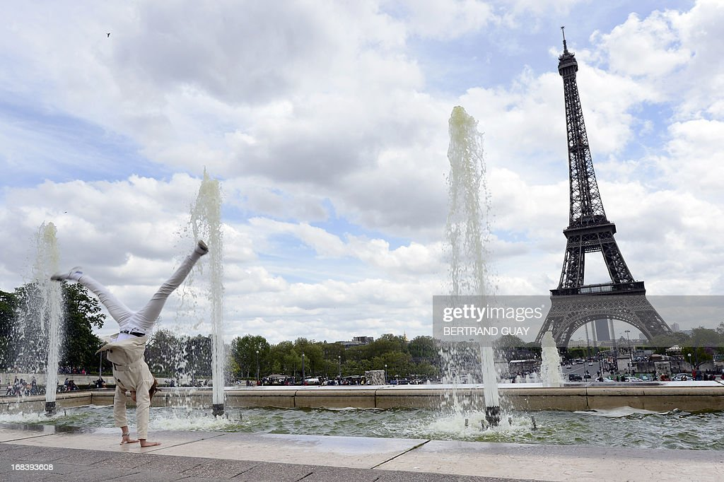 A woman does a cartwheel in front of the Eiffel Tower on May 9, 2013 in Paris.