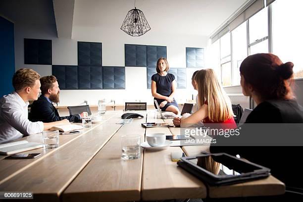 woman does a presentation to team meeting - conferentietafel stockfoto's en -beelden