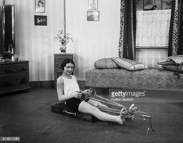 A woman does her daily exercises using a new apparatus which uses many of the muscles of the body ca 1930