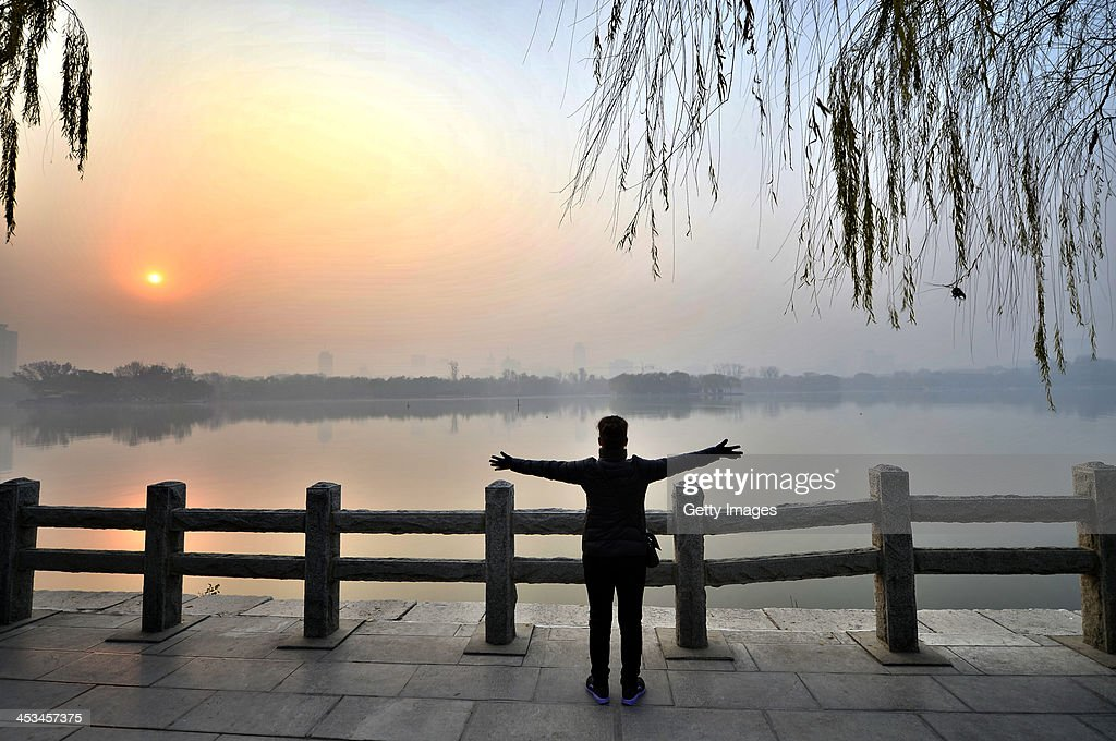 A woman does morning exercises at Daming Lake Park on December 3, 2013 in Jinan, China. China Meteorological Administration issued a yellow warning on smog in some northern and eastern areas on Monday.