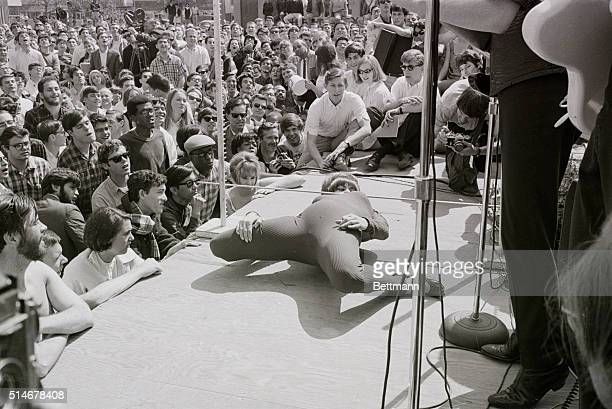 A woman does the limbo on stage in front of a crowd in California