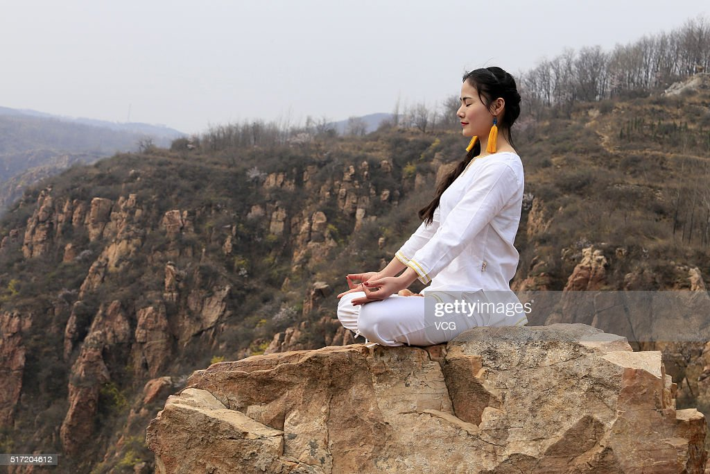 A woman does yoga on the precipice of Mount Song on March 23, 2016 in Zhengzhou, Henan Province of China. Over 10 yoga enthusiasts practice on the precipice to experience stimulation in nature in Zhengzhou.