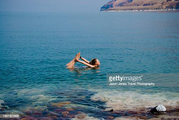 Woman does yoga pose in dead sea