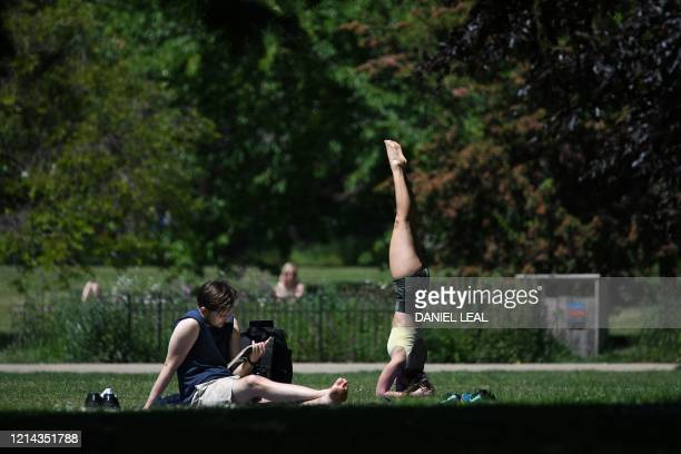 A woman does yoga while people relax in the warm weather in St James's Park in central London on May 21 2020 Hot balmy weather across much of Britain...
