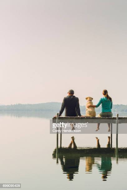 woman, dog and man relaxing on the end of long lake dock. - jetty stock pictures, royalty-free photos & images