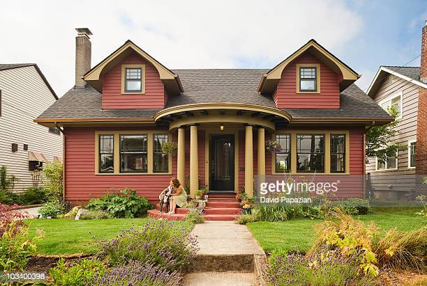 woman & dog sitting on the porch of a quaint house - bungalow stock pictures, royalty-free photos & images