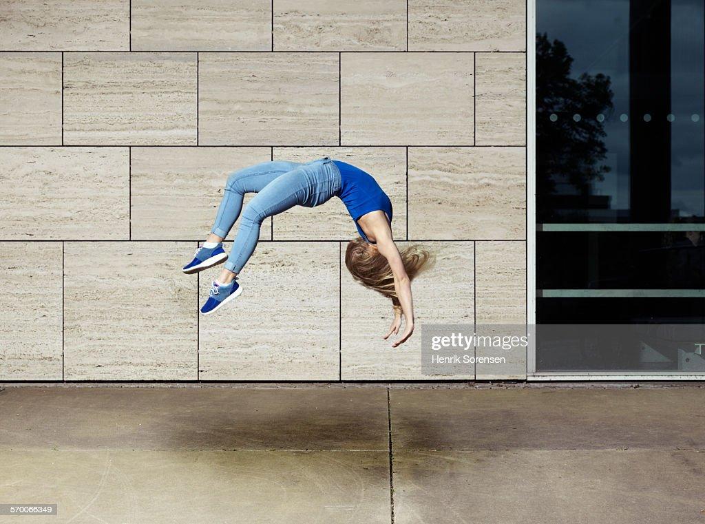 Woman doing a backflip : Stock Photo