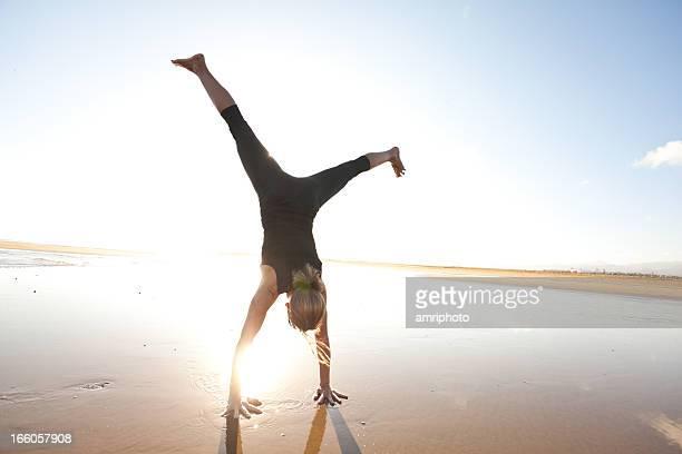 woman doing a cartwheel on the beach