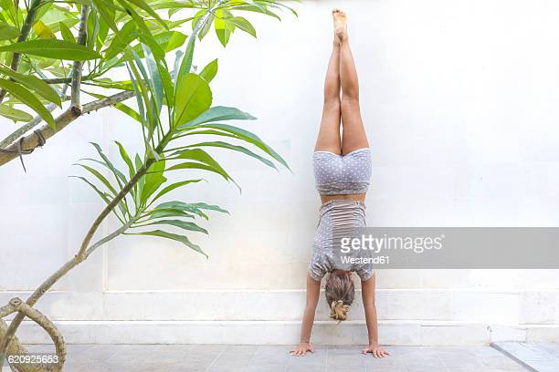 woman doing a handstand at a wall - women in daisy dukes stock photos and pictures
