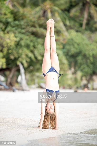 Woman doing a Handstand at the Beach