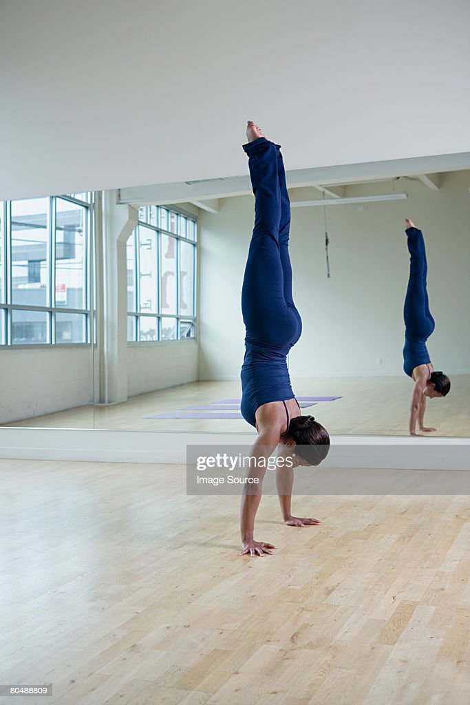 A woman doing a handstand : Stock Photo