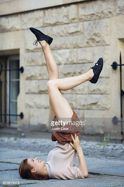 woman doing a shoulder stand in a city street