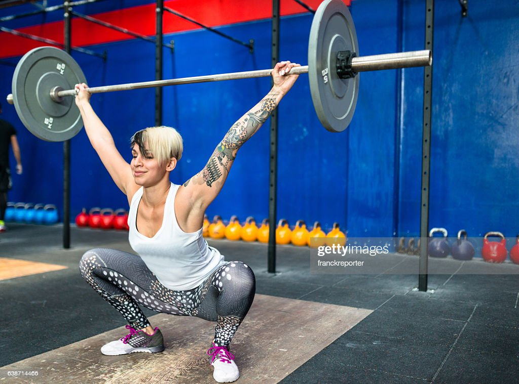 woman doing a strong training with the barbell : Stock Photo