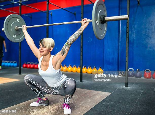woman doing a strong training with the barbell - snatch weightlifting stock photos and pictures